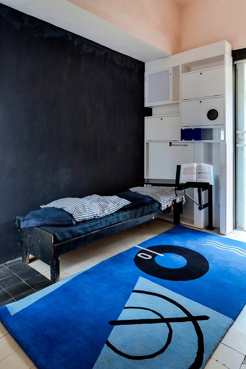 La alcoba en la sala de estar con cabecero, almohada armario y bandeja de libro, restaurado a su condición original, y la alfombra Marine diseñada por Gray