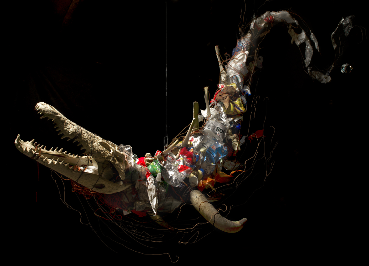 """Sea Animal (2013). Hanging sculpture wich recalls to a sea animal. 2,3x1,5m. Crocodile skull, bull horns, bovine vertebrae, wire and garbage. Exhibition """"Toxic Life. We are nature in toxic evolution"""". Photography © Carlos Bellvehí"""