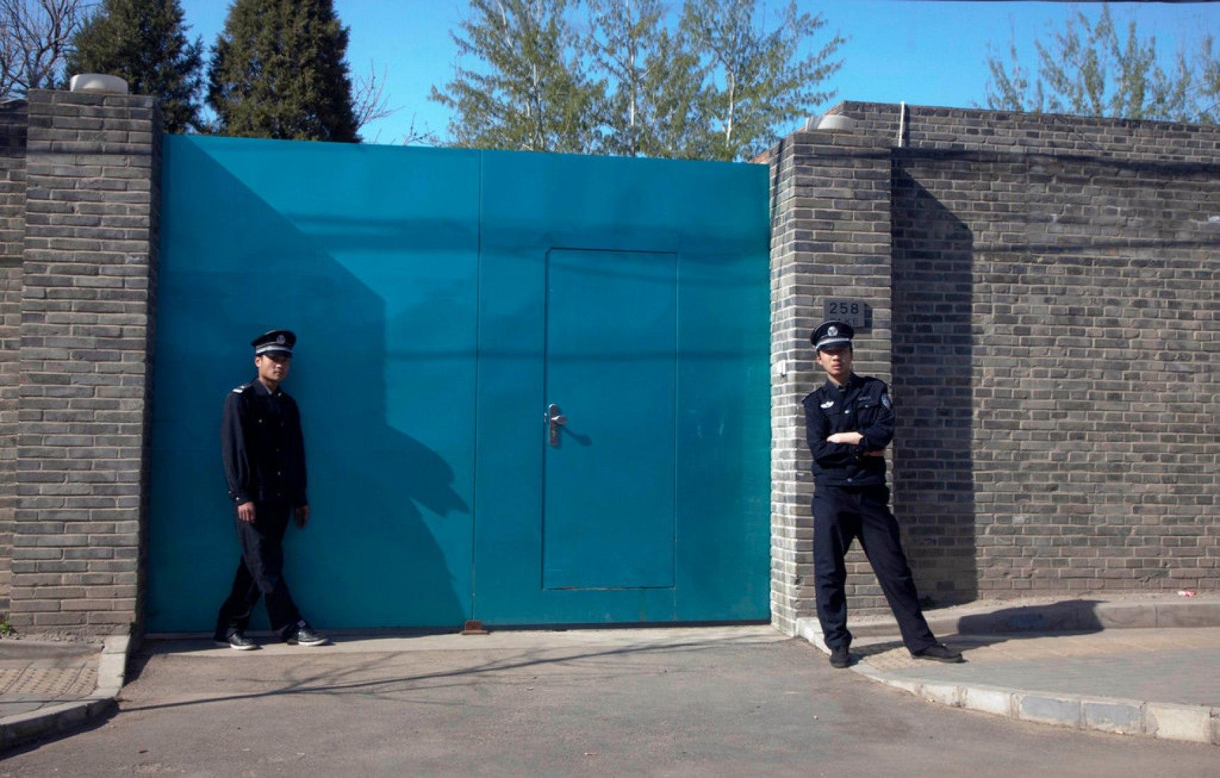 Un oficial de la policia, a la derecha, y un guardia de seguridad en el exterior de la entrada del estudio de Ai Weiwei en Pekín el domingo. Fotografía © Ng Han Guan