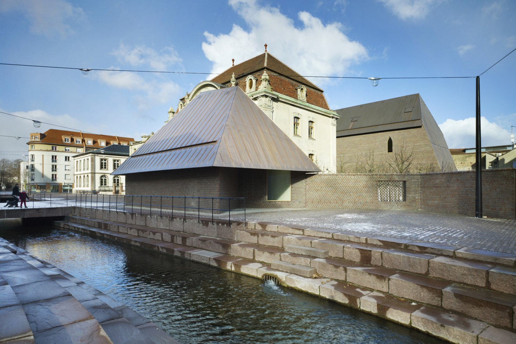 A small building referred to as 'la maison' sits close to the channel. The Musée Unterlinden extension by Herzog & de Meuron. Photograph © Ruedi Walti.
