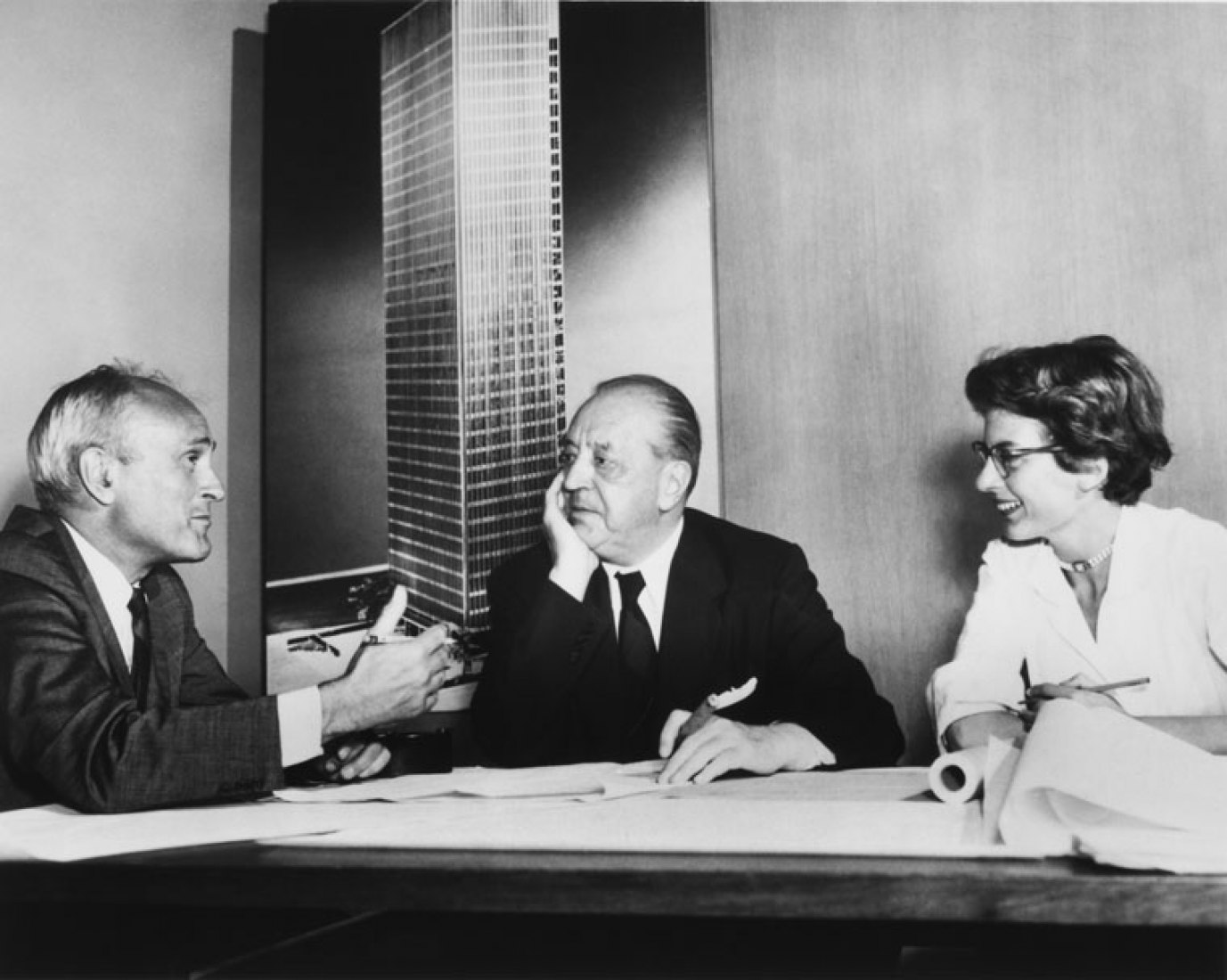 Philip Johnson, Ludwig Mies van der Rohe, and Phyllis Lambert in front of an image of the model for the Seagram building, New York, 1955. Gelatin silver print, 7 1/2 × 9 3/8 in. Photographer unknown. Fonds Phyllis Lambert, Canadian Centre for Architecture, Montreal. © United Press International.