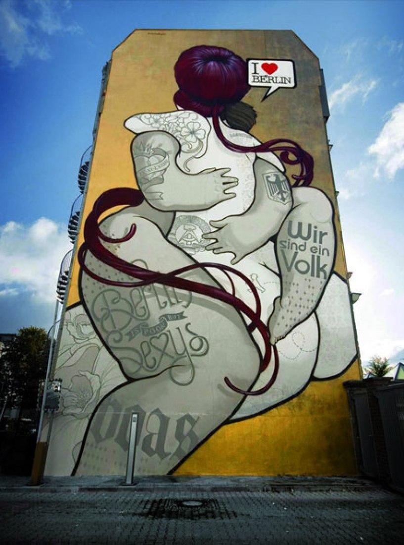 Die Umarmung, del colectivo madrileño BoaMistura. Berlín, 2009. Dos amantes tatuados, con símbolos del oeste uno, del este el otro, se funden en un abrazo. Homenaje al diálogo y entendimiento pintado frente a los restos del viejo muro en el 20° aniversario de la caída.