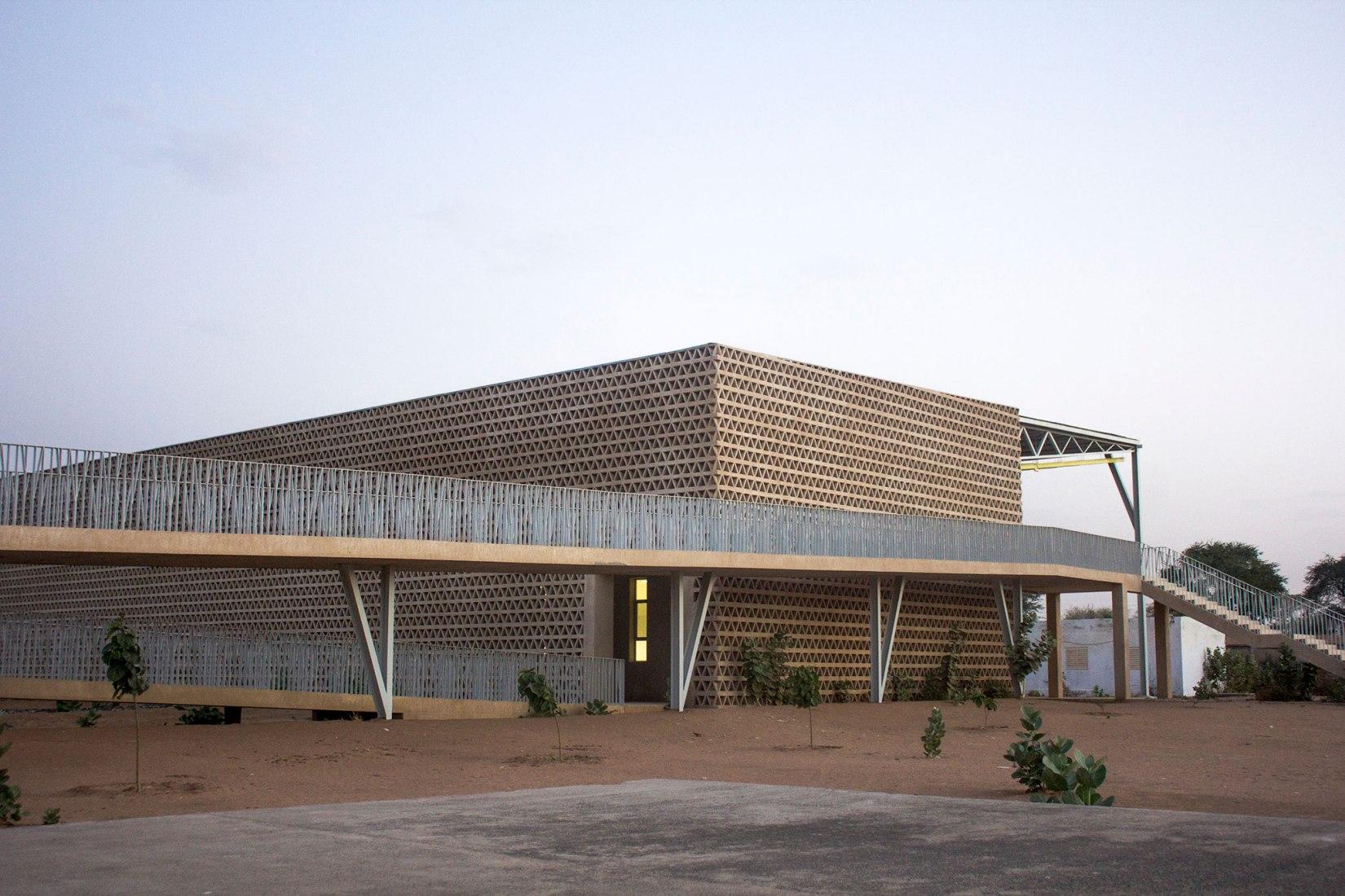 Vista de rampas de acceso y fachada. Edificio de conferencias de la Alioune Diop University por IDOM. Fotografía © Aga Khan Trust for Culture / Chérif Tall.