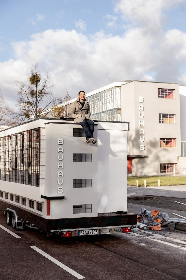 The Wohnmaschine, a tinyhouse version of the Dessau bauhaus conceived by Van Bo Le-Mentzel, in front of the original workshop wing. The miniature version will be home, platform, stage and library during the programme in Dessau. Photograph by  Mirko Mielke