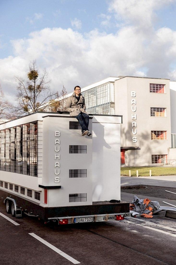 La Wohnmaschine, una versión diminuta de la bauhaus Dessau concebida por Van Bo Le-Mentzel, frente al ala original del taller. La versión en miniatura será el hogar, la plataforma, el escenario y la biblioteca durante el programa en Dessau. Fotografía de Mirko Mielke.