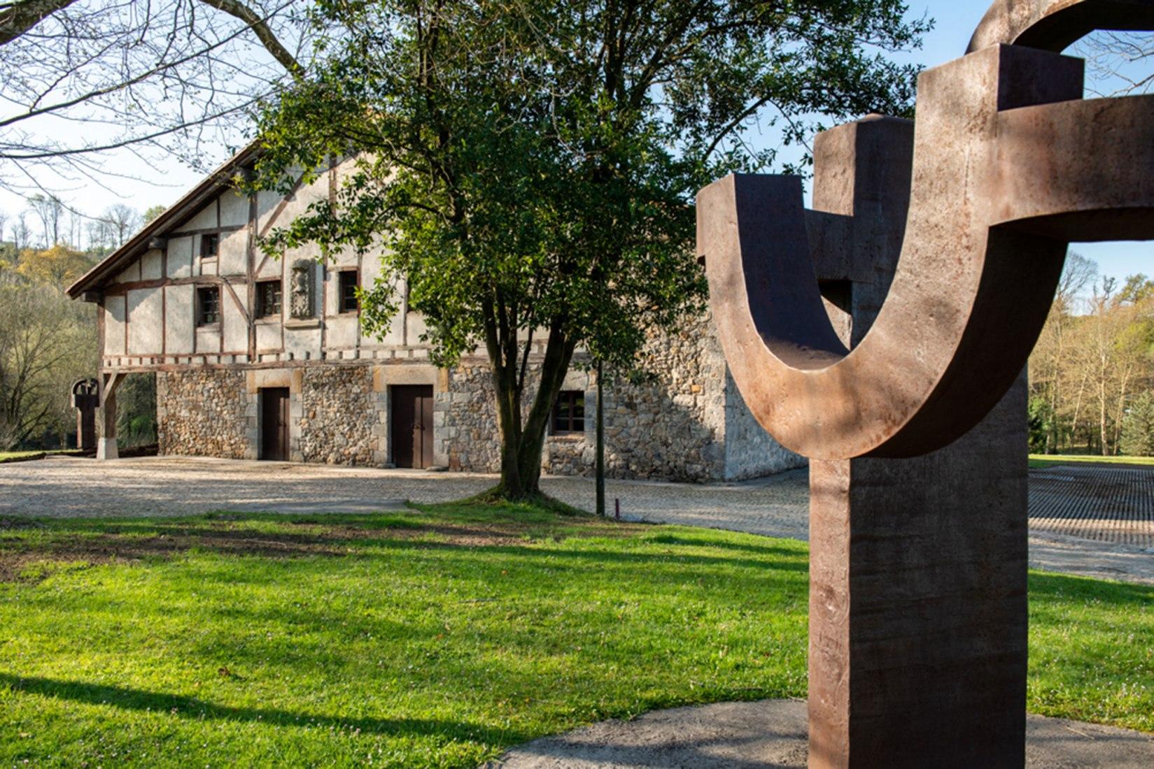 Detail of 'Arch of freedom' ('Arco de la libertad') (corten steel,1993) in front of Zabalaga Farm House 16th century. ©Zabalaga Leku. San Sebastián, VEGAP, 2019. Estate of Eduardo Chillida and Hauser & Wirth. Photo Iñigo Santiago.