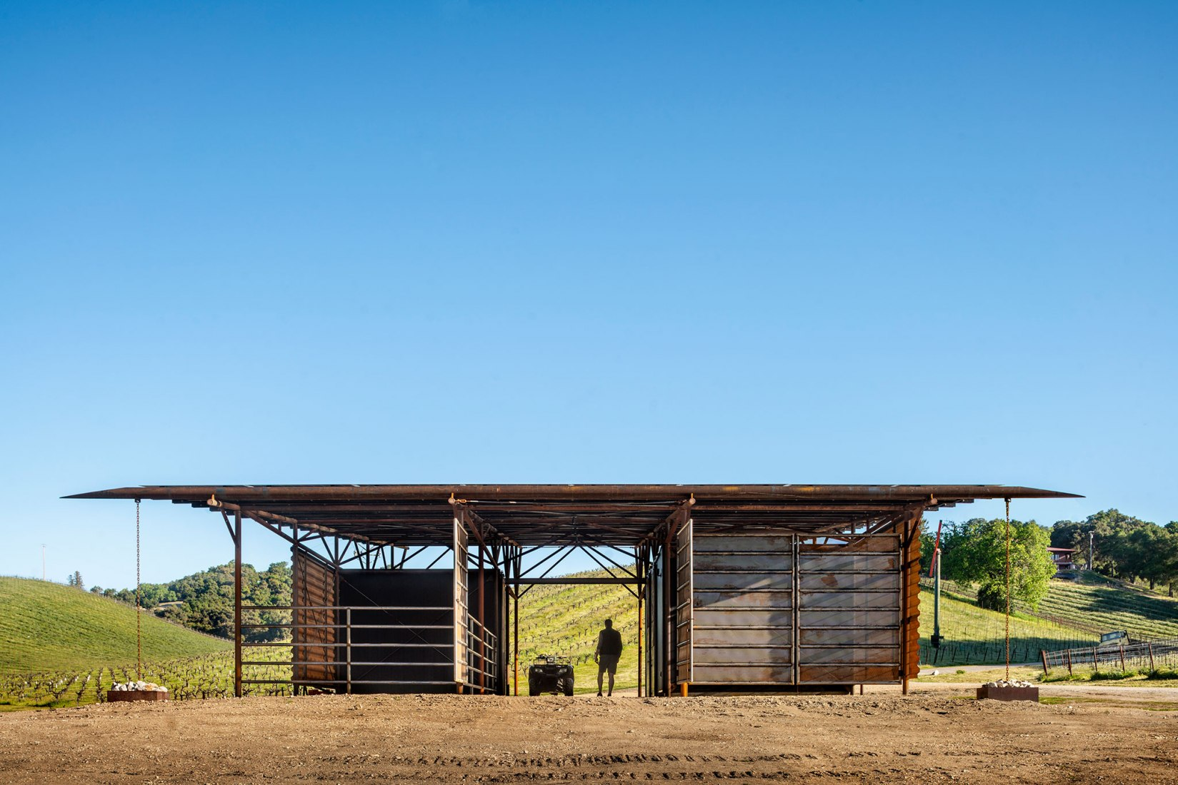 A half pipe steel gutter directs rainfall to chain downspouts and cistern catch basins. Saxum Vineyard Equipment Barn by Clayton & Little Architects. Photograph by Casey Dunn