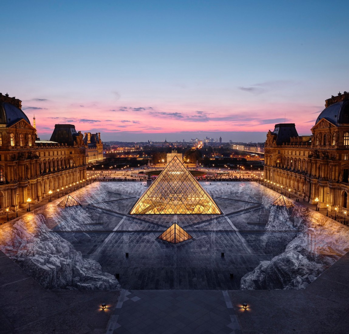 Night view. Artist JR creates a large-scale optical illusion at the Louvre Pyramid, for its 30th birthday