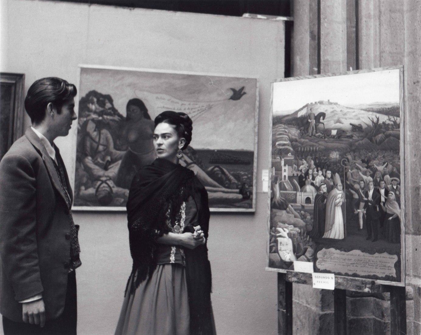 Frida Kahlo y Arturo Estrada en una exposición. Fotografía por Lola Álvarez Bravo (1944).