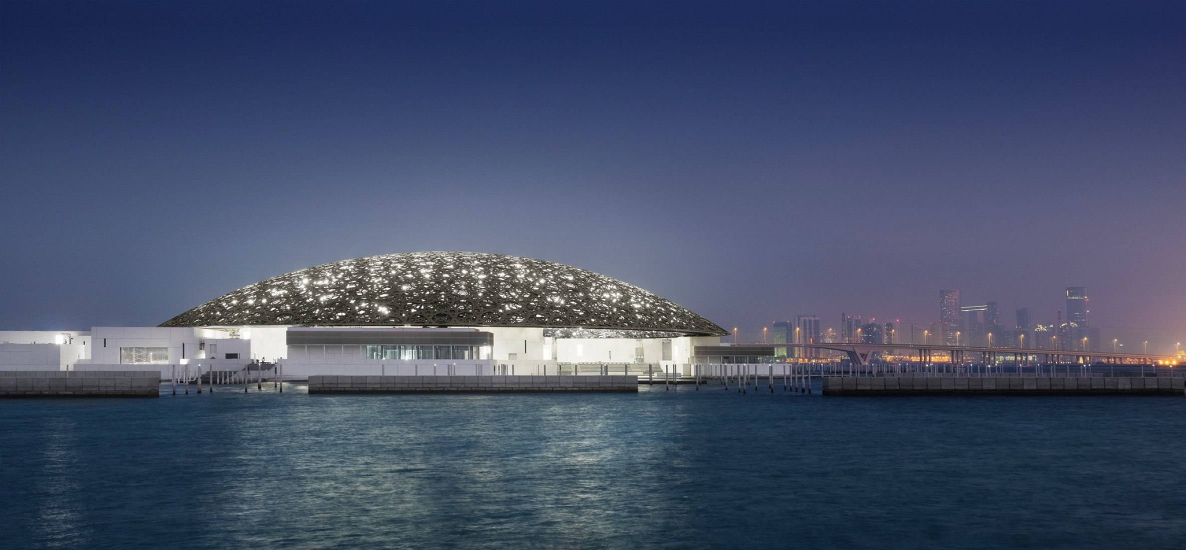 Exterior with Abu Dhabiís Skyline (night). Louvre Abu Dhabiís by Jean Nouvel. Photograph © Louvre Abu Dhabi, Photography: Mohamed Somji