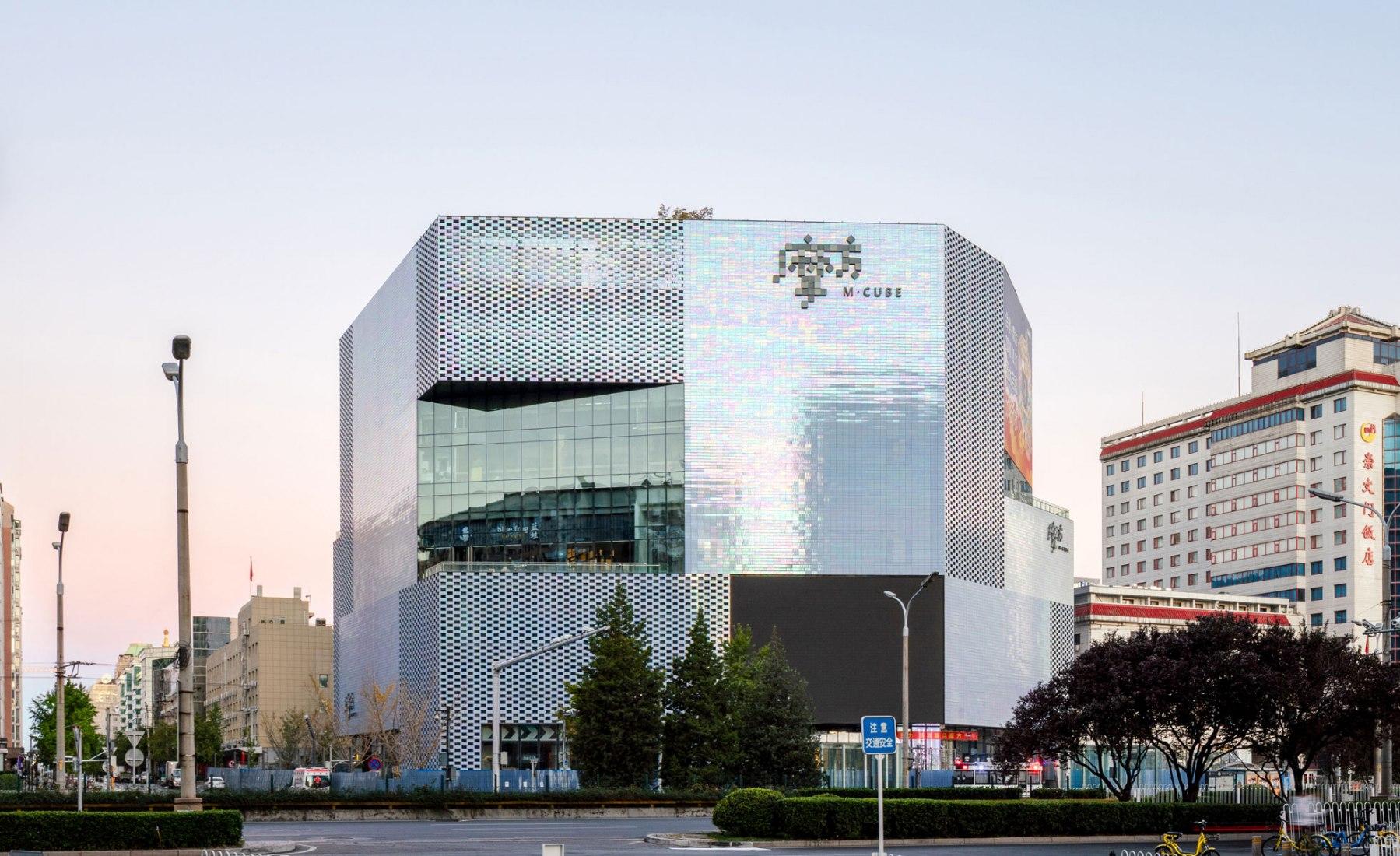 Las fachadas del edificio pueden aparecer silenciadas en gris o reflejar un espectro de colores según el ángulo de visión. KWG · M · CUBE, centro comercial diseñado por MVRDV. Fotografía por Seth Powers
