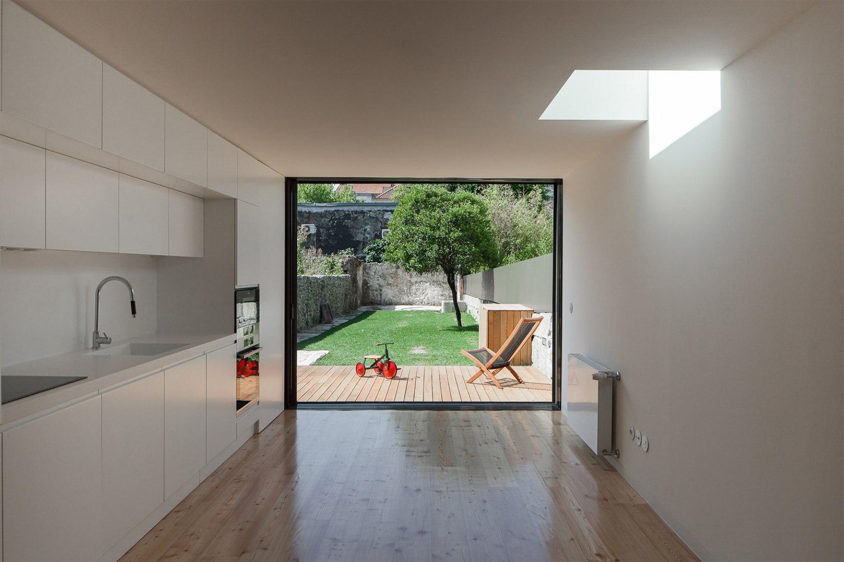 Casa Boavista por Pablo Pita Architects. Vista interior de la zona social, cocina hacia la terraza. Fotografía © José Campos.