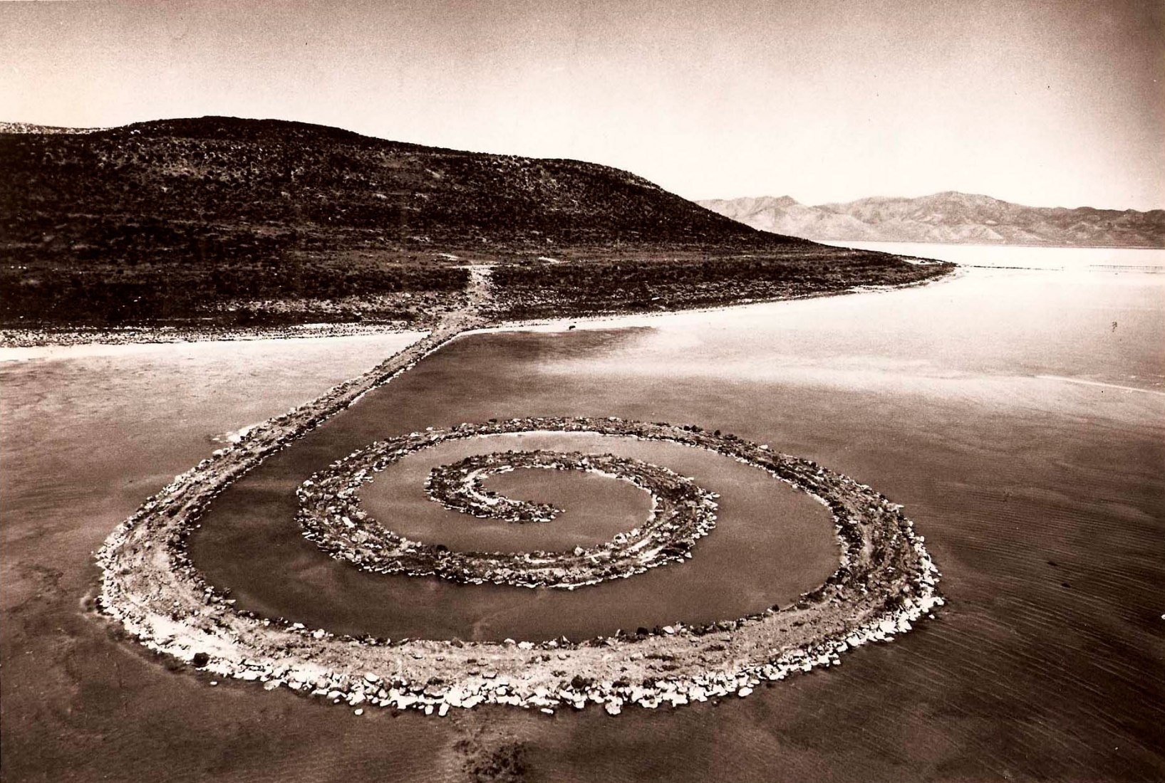 Robert Smithson's earthwork Spiral Jetty (1970) is located at Rozel Point peninsula on the northeastern shore of Great Salt Lake. Using over six thousand tons of black basalt rocks and earth from the site, Smithson formed a coil 1,500 feet long and 15 feet wide that winds counterclockwise off the shore into the water. In 1999, through the generosity of the artist Nancy Holt, Smithson's wife, and the Estate of Robert Smithson, the artwork was donated to Dia Art Foundation.