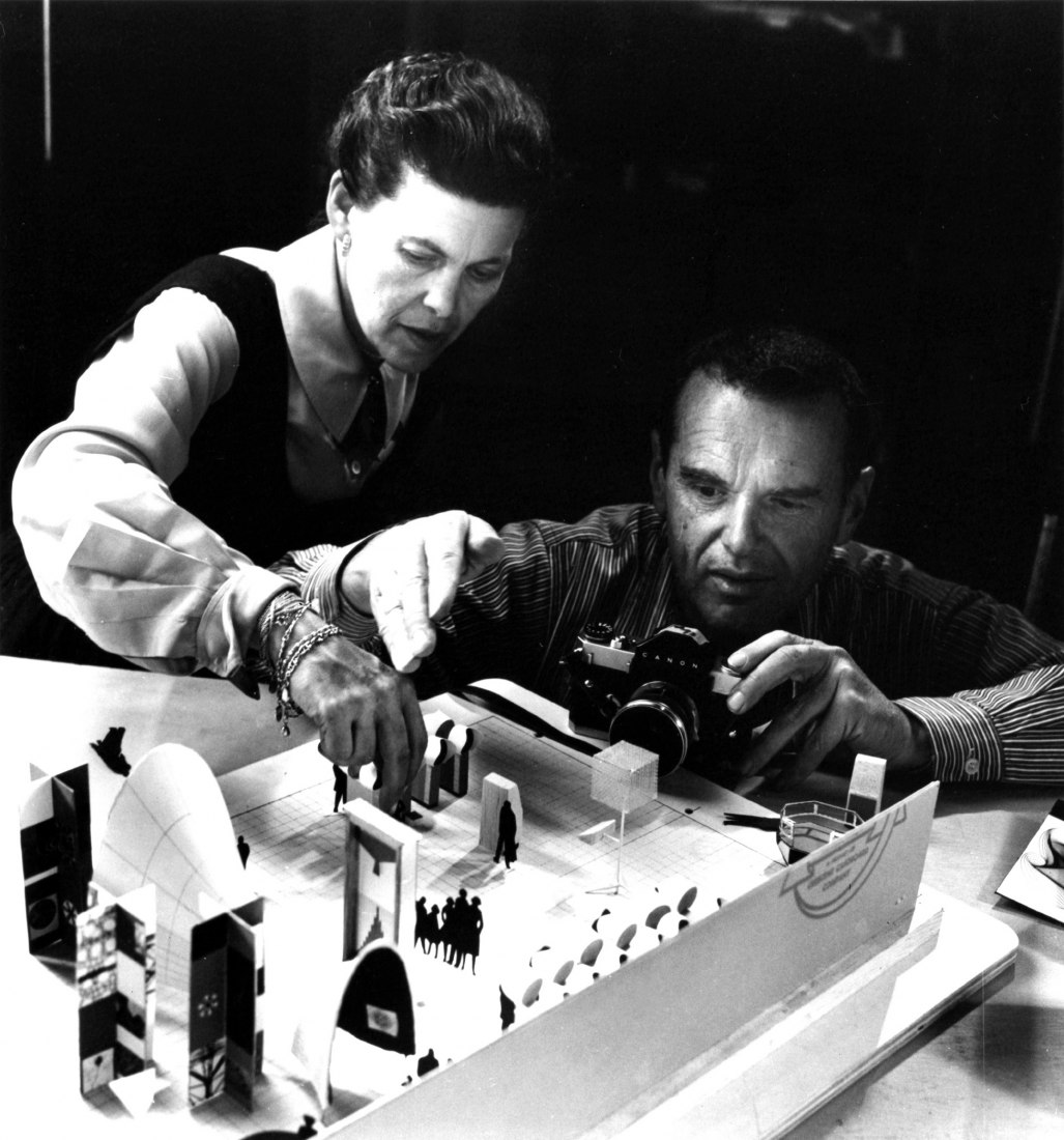 Charles and Ray Eames photographing an early model of the exhibition